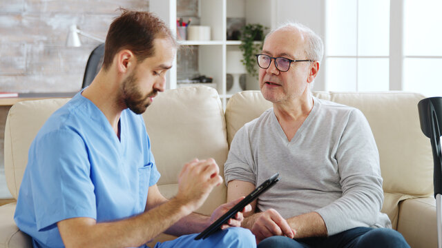 Caucasian male nurse talking with a nursing home patient about his health. The nurse is making notes on a digital tablet