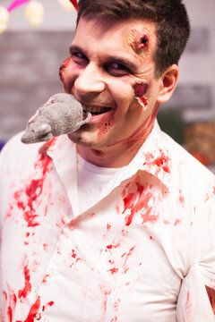 Man dressed up like a bloody zombie with a rat in his mouth at halloween celebration.
