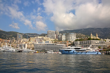 View from the Mediterranean sea of the Principality of Monaco, and Monte Carlo, with dense skyscrapers , the marina, yachts, palace & casino.