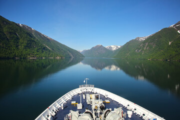 Bow or front of a ship as it cruises down the Sognefjord or Sognefjorden,  Vestland county in Western Norway. Beautiful landscape with reflections in the fjord of the mountains.