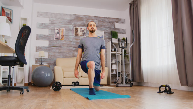 Fit man training his legs doing forward lunges on yoga mat at home.