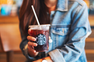 Jun 20th 2020 : Close up of a woman holding and drinking iced coffee at Starbucks coffee shop , Chiang mai Thailand
