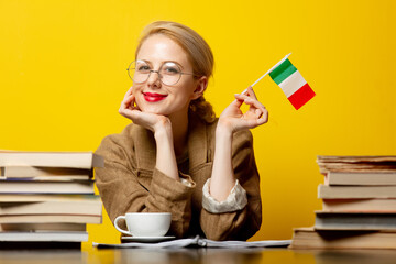 blonde woman with flag of Italy and books on yellow background