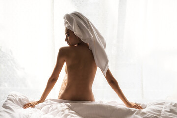Naked woman relax on bed after showering