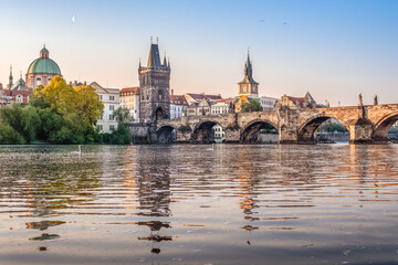 Charles Bridge over the Vltava river with swans during early morning sunrise with still visible moon on the sky, Prague, Czech Republic