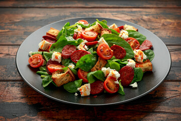 Poster Pierre, Sable Chorizo Tomato salad with spinach, feta cheese and croutons on black plate. healthy summer food