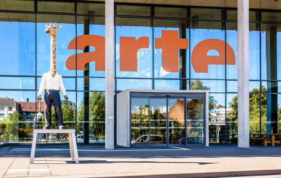 "Strasbourg, France - September 13, 2019: Headquarters of franco-german TV channel Arte with a sculpture by german artist Stephan Balkenhol titled ""Der Giraffenmann"" / ""L'homme-girafe"" (Giraffe Man)."