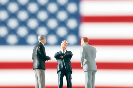 Discussion and negotiation in politics concept: Miniature politician figurines discussing about a subject in front of defocused United States of America flag. Business world concept with businessmen.