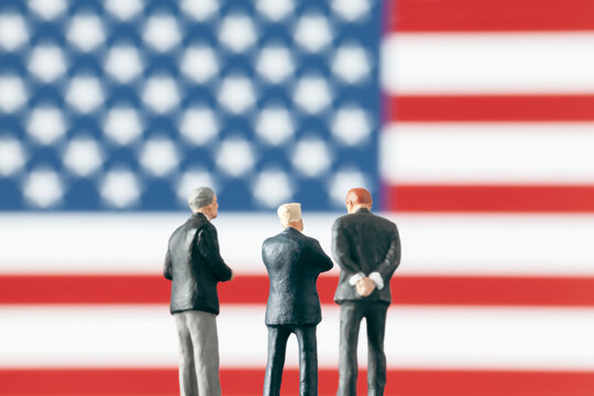 Conflict or discussion in politics concept.: Miniature politician figurines discussing about a subject in front of defocused United States of America flag. Business world concept with businessmen.