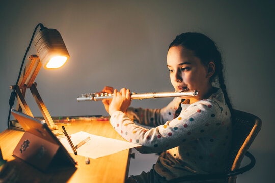 Remote music lesson. Girl playing the flute at home at the night.
