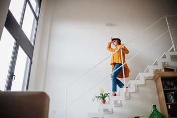 Adult woman going downstairs at home - Lovely woman cheerful on staircase