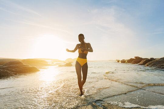 Woman in bikini coming out of the sea dancing