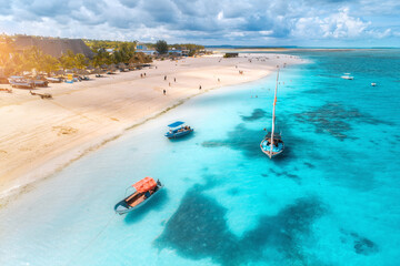 Aerial view of the fishing boats on tropical sea coast with sandy beach at sunrise. Summer holiday in Zanzibar, Africa. Landscape with boat, yacht, clear blue water, green palm trees. Top view. Travel