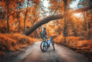 Woman riding a bicycle in  forest in autumn at sunset. Colorful landscape with sporty girl with...