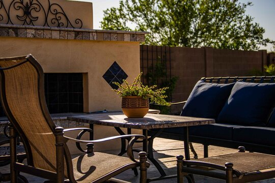 A travertine tile pool deck with plants and lounge chairs in the Arizona southwest .