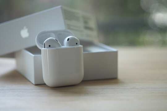 Samut Prakan, Thailand - June 21, 2020 : Apple AirPods wireless headphone with charging box. Use with Iphone, Ipad or Mac.