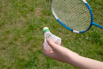 Badminton game with a shuttlecock on the nature. Child holds shuttlrcock  on green grass background
