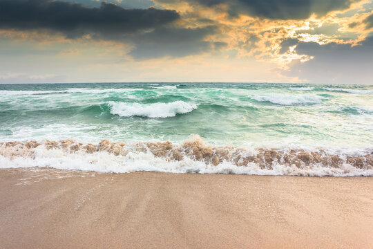 storm on the sandy beach at sunset. dramatic ocean scenery with cloudy sky. rough water and crashing waves in evening light