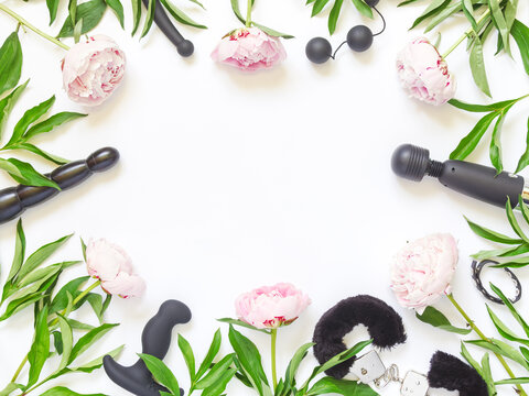 Flower layout for a sex shop. Various sex toys (didlo, handcuffs, balls and other) are on a white background. The background is decorated with pink peonies. Flat lay. Copy space.