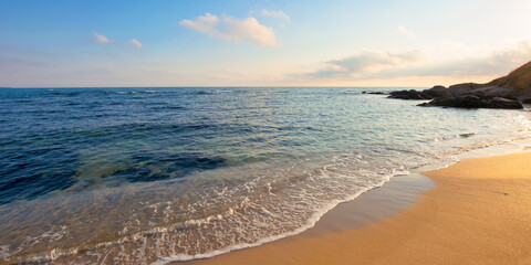 sunrise on the beach. rocks on the sandy shore. sunny weather with some clouds. calm seascape in the morning. beautiful nature scenery