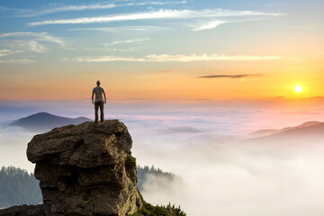 Small silhouette of hiker man enjoying beautiful sunrise in morning mountains. Traveler with raised...