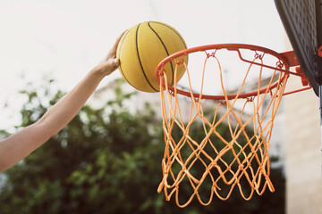 A hand playing Basketball ball in the basketball hoop