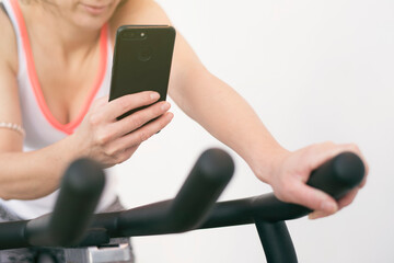 Sportswoman looking phone on spinning bike