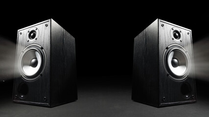 Two sound speakers with free space between them on black background.