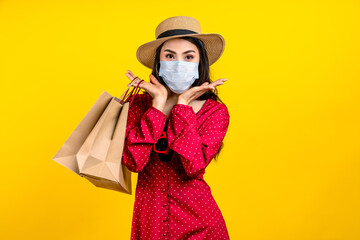 Portrait of young happy carefree asian woman wear hat and facemask carrying shop bag smile on isolated color background in concept back to shopping, new normal summer fashion lifestyle after covid19.
