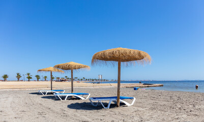 End of June 2020 at the Mar Menor in Spain on the east coast. The beach with straw parasols is almost empty. Few people during the Corona period despite the sunshine.