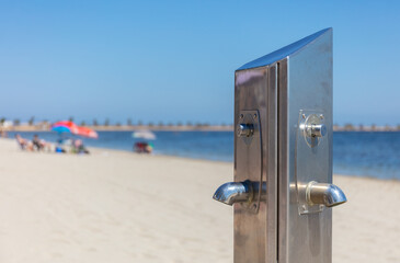 At the Mar Menor in Spain there is a silver water dispenser for cleaning on the beach. It is lonely here, because of the Corona virus crisis there are still no tourists, despite the sun and the sea.
