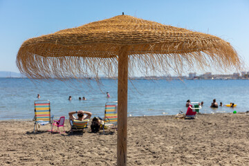 An umbrella on the beach in late June 2020 at the Mar Menor in Spain on the east coast. Few people are here despite the sunshine. There are still no tourists during the Corona period.