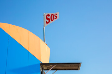 An SOS flag shows that there is a rescue station on the beach. The lifeguard station is located in Spain at the Mar Menor. The sun is shining with a blue sky.
