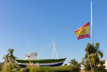 The Spanish flag at half mast. It is the time of mourning for the victims of the Corona Virus crisis. The scene is a roundabout with a fishing boat as decoration.