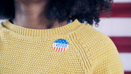 Black woman with I Voted sticker after voting in the 2020 election