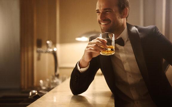 Smiling man having whiskey at night club