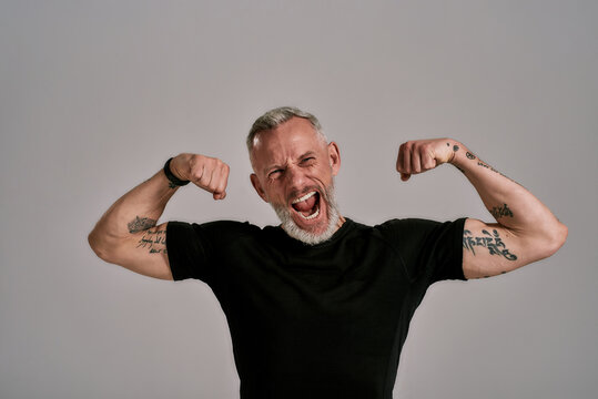 Be more, do more. Angry middle aged muscular man in black t shirt shouting at camera, showing his biceps while posing in studio over grey background