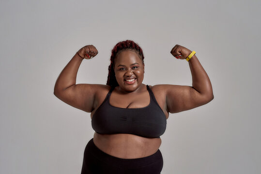 Enjoy your body. Plump, plus size african american woman in sportswear smiling at camera, showing strong arms in studio over grey background. Concept of sport, healthy lifestyle, body positive