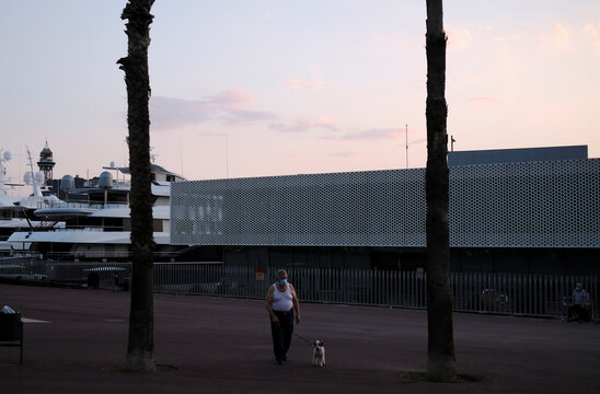 Elderly man wearing a protective face mask walks with his dog, as Spain officially reopens the borders amid the coronavirus disease (COVID-19) outbreak, in Barcelona
