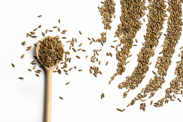 Wooden spoon with brown grains of wheat on pure white isolated background on left side. Stripes rows of cereal seeds in the upper corner like an agricultural field. Oats rye barley close-up. Top view Papier Peint