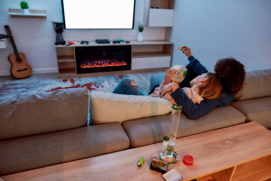 Back view of young couple watching TV together, eating snacks after smoking marijuana from a bong or glass water pipe. They relaxing on the couch in the evening at home