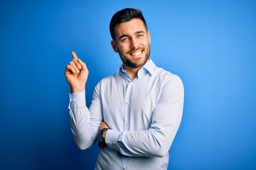Young handsome man wearing elegant shirt standing over isolated blue background with a big smile on...