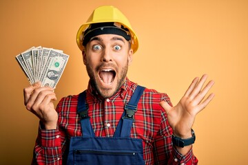 Young builder man wearing safety helmet holding dollars as payment over yellow background very...