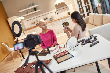 Believe In Beauty. Asian beauty blogger taking pictures of woman before applying makeup on her face using cosmetic products on the table. Two women recording video for social network