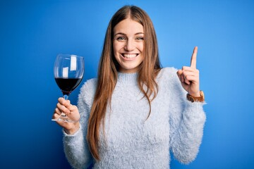 Young beautiful redhead woman drinking glass of red wine over isolated blue background surprised...