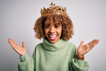 Young african american woman wearing golden crown of queen over isolated white background celebrating crazy and amazed for success with arms raised and open eyes screaming excited. Winner concept