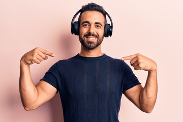 Young hispanic man listening to music using headphones looking confident with smile on face,...