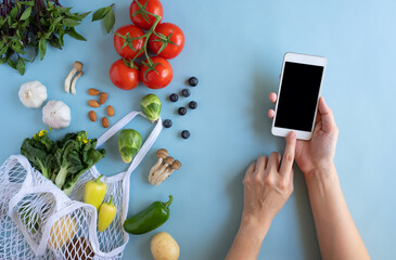 nutrition on mobile phone for diet food  and meal. flat lay of  healthy vegetable . blue background.