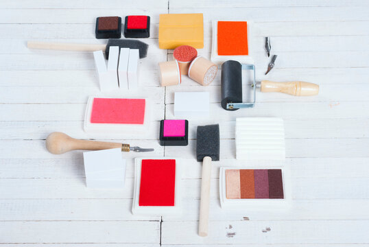 handicraft equipments, ink pads, lino cutter, paint roller and plasticine blocks on white wood table