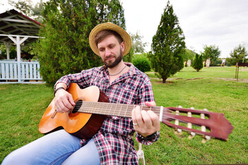 a young bearded man in a checked shirt and a straw hat plays a guitar and smiles sitting on a chair against the background of a Park, green grass and a gazebo. Outdoor recreation, weekend
